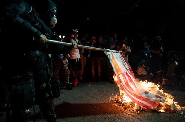 США: Протестующие сжигают библию и американский флаг в Портленде